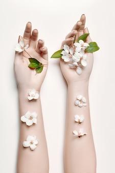 Moda arte mão mulher no verão e flores na mão com maquiagem contrastante brilhante. meninas de mão de foto de beleza criativa sentadas à mesa em fundo contrastante com sombras coloridas. cuidados com a pele