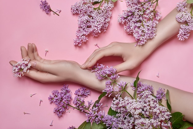 Moda arte mãos mulheres de cosméticos naturais, flores lilás roxas brilhantes na mão com maquiagem de contraste brilhante, cuidados com as mãos. foto de beleza criativa de uma garota sentada à mesa em um fundo rosa contrastante