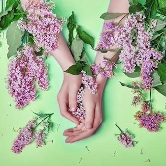 Moda arte mãos mulheres de cosméticos naturais, flores lilás roxas brilhantes na mão com maquiagem de contraste brilhante, cuidados com as mãos. foto de beleza criativa de uma garota sentada à mesa em um fundo verde contrastante