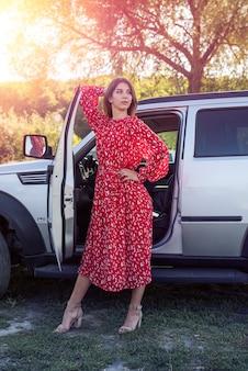 Moda atraente mulher com vestido vermelho de verão em pé perto dela, carro off road, estilo de vida