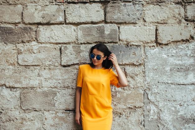 Moda atraente mulher em um vestido amarelo com óculos escuros posando perto de uma parede branca