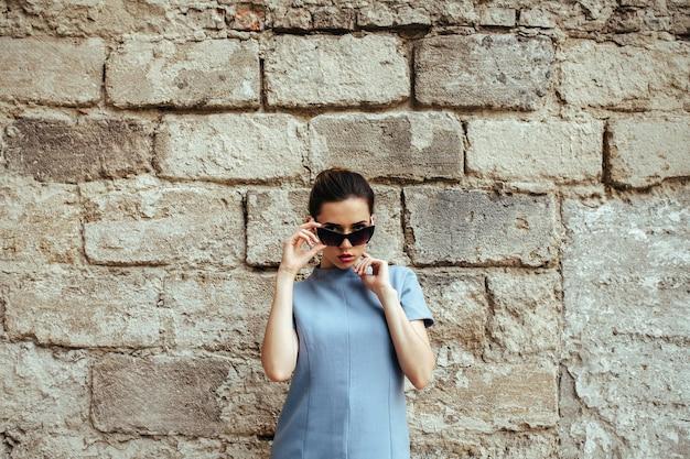 Moda atraente mulher em um vestido azul com óculos escuros posando perto de uma parede branca