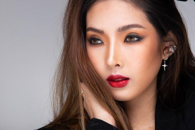 Moda beleza mulher tem cabelo loiro longo e reto olha para a câmera e expressa o sentimento. retrato de menina asiática usando vestido preto sobre parede cinza, copie o espaço