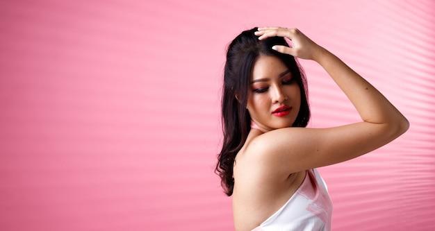 Moda beleza mulher tem cabelo preto e expressa sentimento de choro triste. retrato de uma menina asiática usando um vestido rosa sobre uma parede de tom rosa e se sentar na cadeira do banquinho, copie o espaço