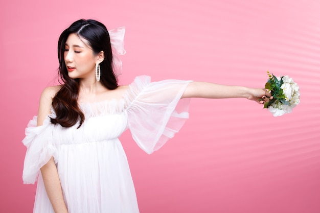 Moda beleza mulher tem cabelo preto expressar sentimento de raiva. menina asiática usa vestido rosa sobre tom de rosa, segura a flor na parede e tenta se reconciliar com o namorado, copie o espaço