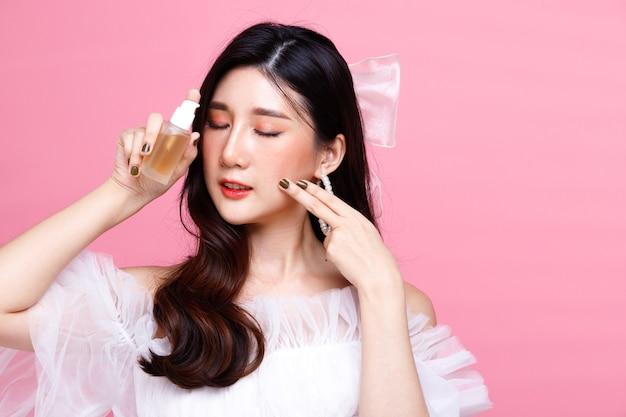 Moda beleza mulher tem cabelo preto expressar sentindo amor feliz. menina asiática usa vestido rosa sobre tom de rosa na parede segura a loção de beleza para a pele e aplica no rosto, mão, copie o espaço