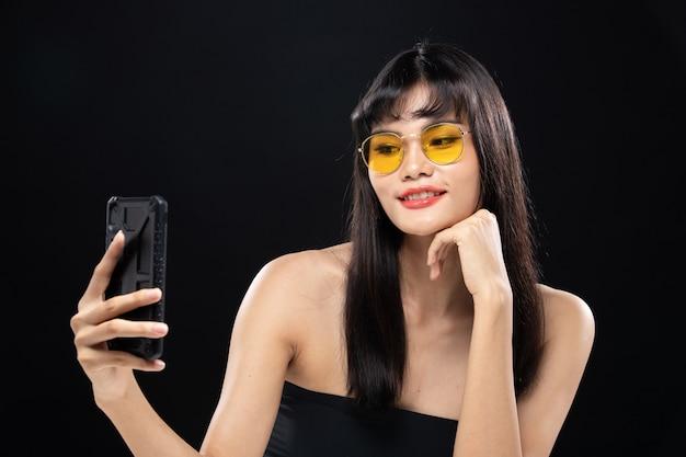 Moda beleza mulher tem cabelo preto longo e reto olha para a câmera e expressa o sentimento. retrato de menina asiática usando telefone inteligente sobre parede preta, copie o espaço
