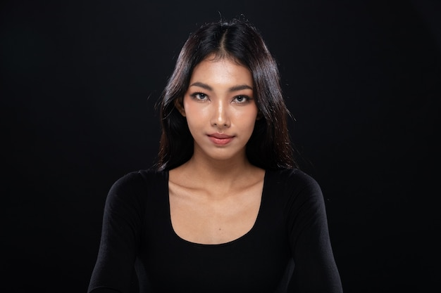 Moda beleza mulher tem cabelo preto longo e reto olha para a câmera e expressa o sentimento. retrato do rosto forte de uma menina asiática sobre uma parede preta, copie o espaço