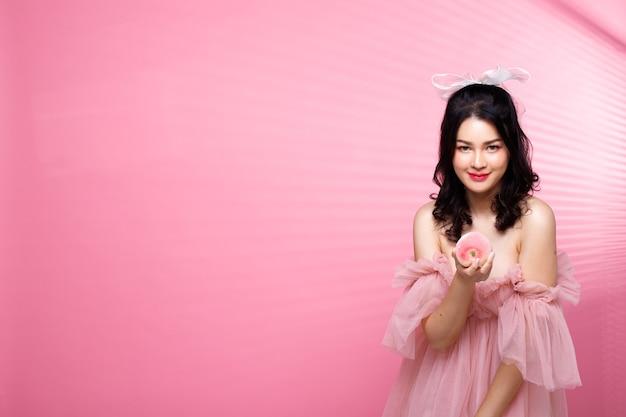 Moda beleza mulher tem cabelo preto olha para a câmera e expressa um sorriso de sentimento. retrato de uma menina asiática usando um vestido rosa sobre uma parede em tom de rosa com uma janela com listras na parede à tarde, copie o espaço