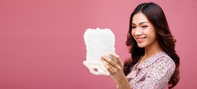 Moda beleza mulher tem longos cabelos negros expressar sentimento emoção sexy. retrato de menina asiática usando um vestido rosa e segurando um espelho com um grande sorriso na parede rosa, copie o espaço