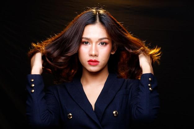 Moda beleza mulher tem longos cabelos negros expressar sentimento emoção sexy. retrato de menina asiática usando vestido azul escuro esvoaçantes cabelos no ar sobre a parede preta, copie o espaço