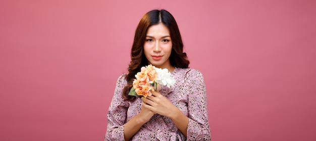 Moda beleza mulher tem longos cabelos negros expressar sentimento emoção sexy. retrato de menina asiática usando vestido rosa e segurando um buquê de flores por amor na parede rosa, copie o espaço