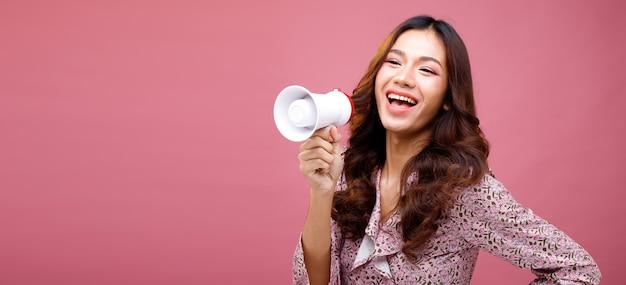 Moda beleza mulher tem longos cabelos negros expressar sentimento emoção sexy. retrato de menina asiática usando vestido rosa e segurando um megafone para anunciar na parede rosa, copie o espaço