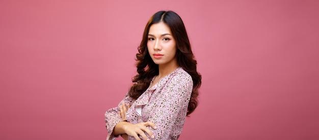 Moda beleza mulher tem longos cabelos negros expressar sentimento emoção sexy. retrato de menina asiática usando vestido rosa sobre parede rosa, copie o espaço