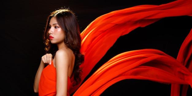 Moda beleza mulher tem longos cabelos negros expressar sentimento emoção sexy. retrato de menina asiática voando com roupas vermelhas e tecido esvoaçante no ar sobre a parede preta, copie o espaço