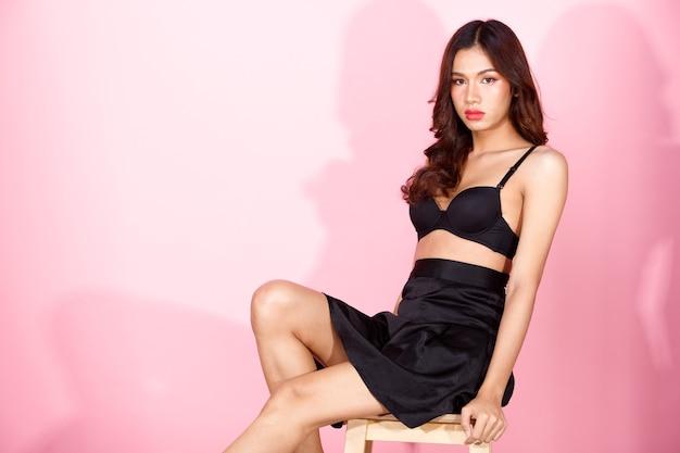 Moda beleza mulher tem longos cabelos negros expressar sentimento emoção sexy. retrato de uma menina asiática usando saia curta preta e senta-se no banquinho, fazendo poses da moda na parede rosa, copie o espaço