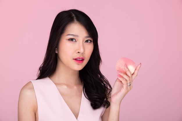 Moda beleza mulher tem longos cabelos negros olha para a câmera e expressa o sentimento de felicidade. retrato de menina asiática usando um vestido rosa e comendo pêssego em uma parede cor de rosa