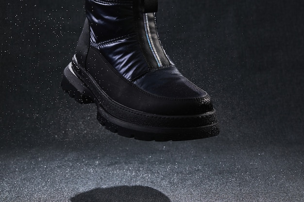 Moda bota preta sem marca com gotas, spray e respingos voando. sapatos femininos modernos para caminhadas off-road.