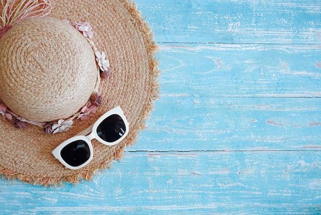 Moda chapéu e óculos para viajar sobre fundo azul de madeira.