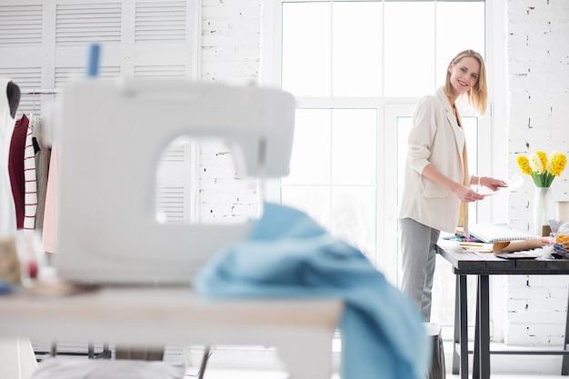 Moda como profissão. artesã feliz e alegre segurando o desenho enquanto olha para a máquina de costura