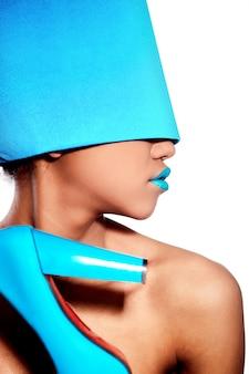 Moda de alta moda look.glamour linda mulher americana negra com lábios azuis brilhantes com material azul na cabeça isolado no branco