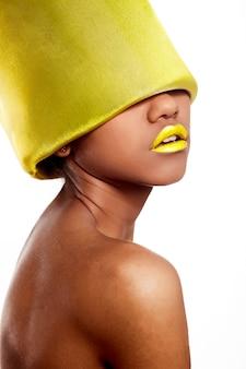 Moda de alta moda look.glamour linda mulher americana negra com lábios brilhantes amarelos com material amarelo na cabeça isolado no branco