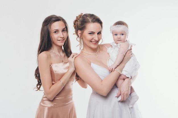 Moda de casamento para mulheres de todas as idades. um grupo de mulheres em longos vestidos de noite em um branco