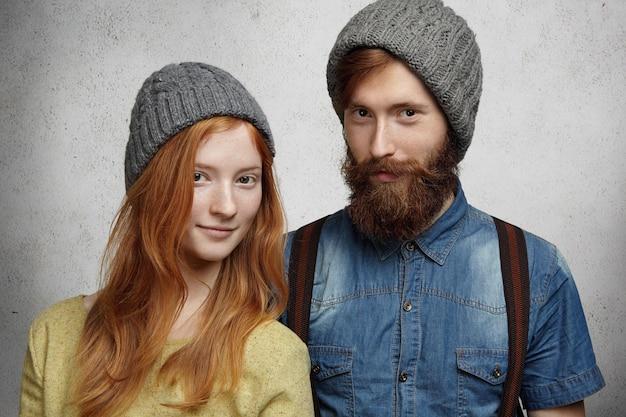 Moda de inverno. jovem casal caucasiano feliz usando chapéus de malha cinza quentes posando dentro de casa contra a parede.