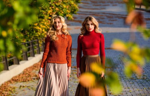 Moda de outono. tendências da moda em saia plissada. mulheres caminhando no parque outono. meninas amigas. roupa elegante de outono. adoráveis senhoras aproveitam o dia ensolarado de outono. roupas da moda. feminilidade e ternura.