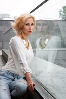 Moda de verão ao ar livre, retrato deslumbrante da bela jovem mulher sexy loira vestida com uma camisa branca e calça jeans rasgada, posando na rua.