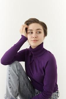 Moda e bela jovem modelo feminina usando blusa de manga longa violeta com gola da tartaruga e jeans largos posando na parede branca, apoiando o cotovelo no joelho e olhando para o lado