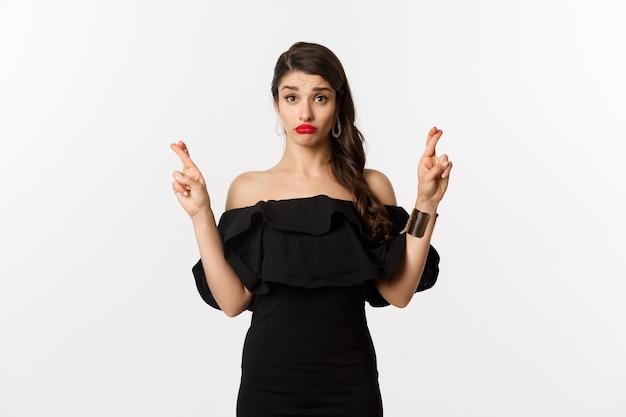 Moda e beleza. esperançosa mulher boba em vestido preto fazendo desejo, segurando os dedos cruzados para dar boa sorte, em pé sobre um fundo branco.