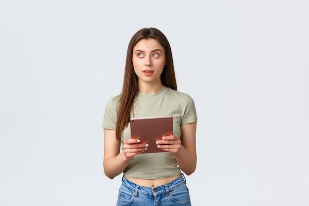 Moda e beleza, estilo de vida e conceito de compras. mulher atraente pensativa em roupa casual, olhando para longe, pensando o que comprar na loja online usando tablet digital, fundo branco.