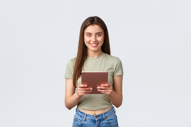 Moda e beleza, estilo de vida e conceito de compras. mulher caucasiana atraente em roupa casual segurando um tablet digital, rolando nas lojas online, fazendo pedidos, fazendo reserva, fundo branco