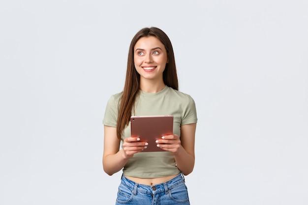 Moda e beleza, estilo de vida e conceito de compras. mulher sonhadora, atraente e elegante, parecendo no canto superior esquerdo com um sorriso satisfeito enquanto usa o tablet digital, fazendo pedidos online