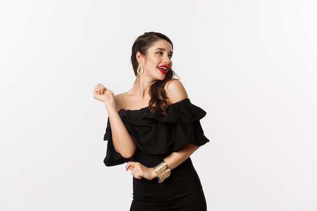 Moda e beleza. mulher comemorando e dançando no vestido preto, se divertindo e sorrindo, em pé sobre um fundo branco.
