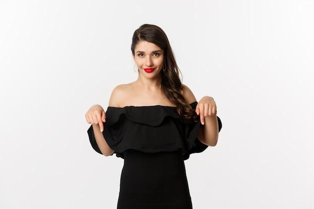Moda e beleza. mulher elegante de vestido preto apontando os dedos para baixo, mostrando a promo e sorrindo, em pé sobre um fundo branco.