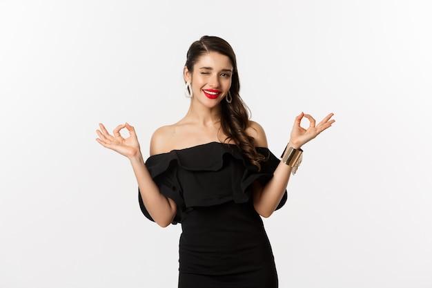 Moda e beleza. mulher morena atraente de vestido preto, mostrando sinais de ok e piscando para a câmera, aprovar e recomendar, em pé sobre fundo branco.