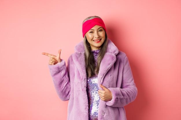Moda e conceito de compras. mulher asiática sênior elegante apontando o dedo esquerdo no negócio da promoção, sorrindo para a câmera, sugerindo oferta especial, de pé contra um fundo rosa.