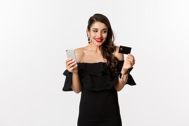 Moda e conceito de compras. mulher bonita feliz comprando online, segurando o cartão de crédito e smartphone, fundo branco.