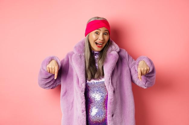 Moda e conceito de compras. mulher idosa asiática empolgada conferindo uma oferta especial, apontando o dedo para baixo e sorrindo feliz para a câmera, mostrando anúncio, fundo rosa