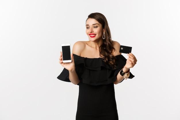 Moda e conceito de compras online. mulher jovem feliz em um vestido preto, mostrando o cartão de crédito e a tela do celular, em pé sobre um fundo branco.