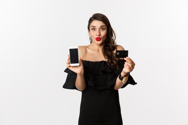 Moda e conceito de compras online. mulher jovem feliz em um vestido preto, mostrando o cartão de crédito e a tela do celular, em pé sobre um fundo branco