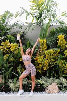 Moda elegante e jovem caucasiana em forma esportiva com blusa de cami leopardo e shorts de motociclista do lado de fora segurando um shaker de proteína