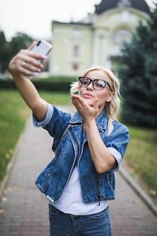 Moda elegante mulher loira em uma suíte jeans faz selfie dar airkiss em seu telefone na cidade pela manhã
