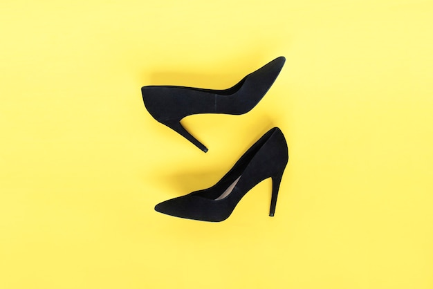 Moda elegante sapatos pretos de salto alto em fundo amarelo vista plana de cima, fundo da moda aparência do blog de moda