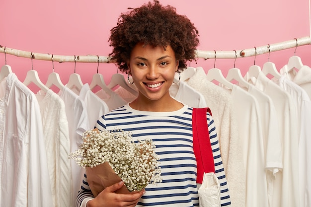 Moda, estilo e conceito de compras. cliente positivo de uma jovem posa em um show perto de roupas brancas como a neve em cabides e escolhe uma nova roupa para uma ocasião especial