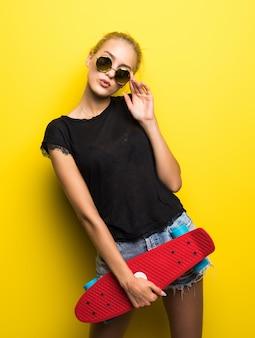 Moda feliz sorridente hipster garota legal em óculos de sol e roupas coloridas com skate se divertindo ao ar livre contra o fundo laranja