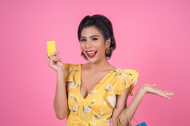 Moda feminina gosta de fazer compras com sacola de compras e cartão de crédito