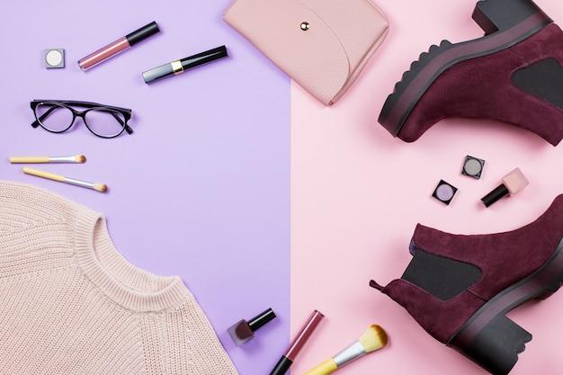 Moda feminina roupas de outono, acessórios e produtos de beleza planos leigos sobre um fundo pastel.